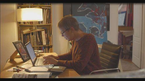 Judit a festményeit mappába rendezi (Vasvári Emese)