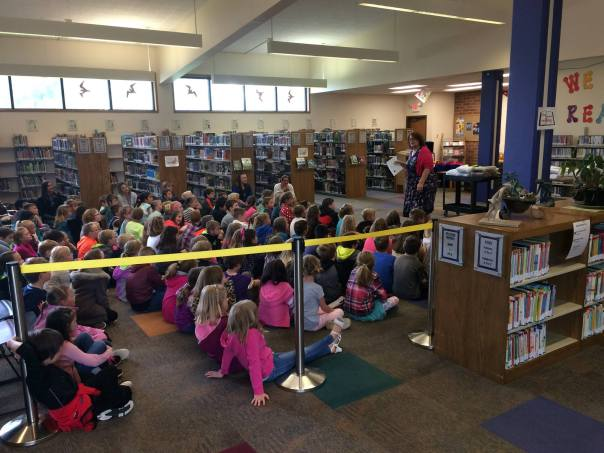 Woman in library reading a book to a large group of children. Library shelves in background.