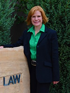 Tawnya standing in green shirt and dark suit by law library sign