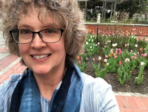 Selfie of Suzanne Reymer with tulips in the background. She's wearing a light blue shirt and glasses and has short, brown, curly hair.