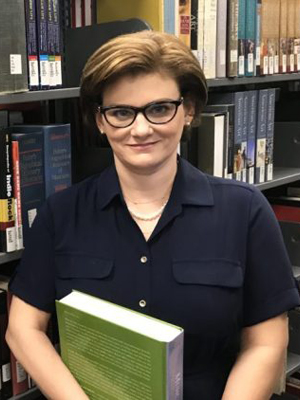 Woman in eyeglasses holding green book in front of bookshelves