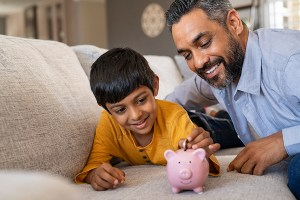 Happy son saving money in piggy bank with father