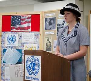 Female student in period dress with hat standing at podium.