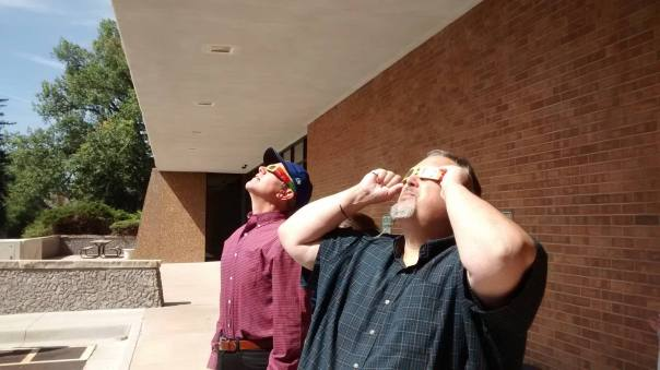 Paul and Thomas standing outside looking up with eclipse glasses on.
