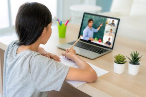 Asian girl student video conference e-learning with teacher and classmates on computer in living room at home.