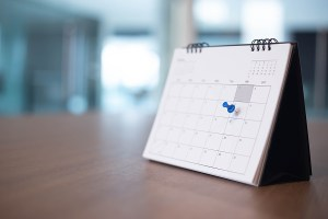 Calendar event planner with pushpin in one box