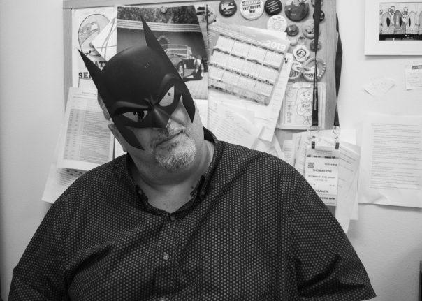 Black and white photo of Thomas in Batman mask
