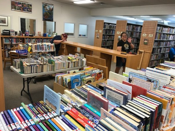 Library interior with many books out on tables instead of on shelves. One staff member waving at camera.