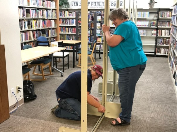 Two women assembling shelving