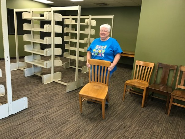 Woman holding wooden chair while standing in front of empty library shelves