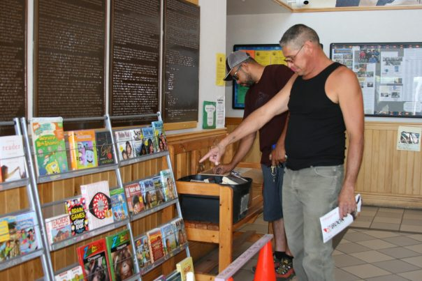 Two men looking at rack full of books