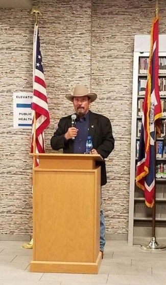 Man in cowboy hat standing at podium with microphone between U.S. and Wyoming flags