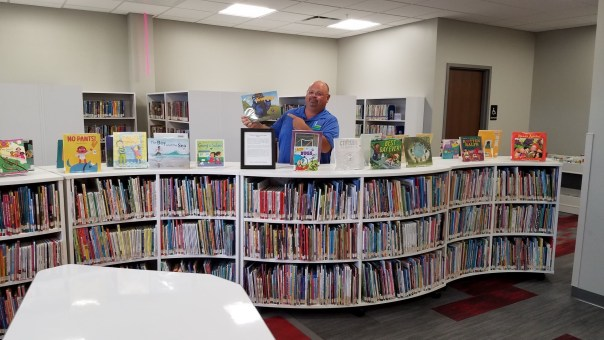 Man holding up picture book, standing behind curvy set of white, waist-high bookshelves. Picture books are on display on top of the shelves.