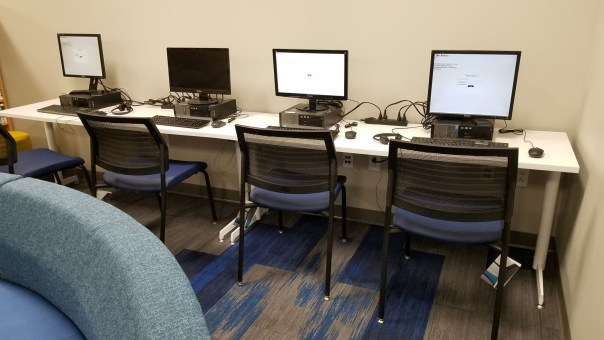 Row of computers with empty chairs.