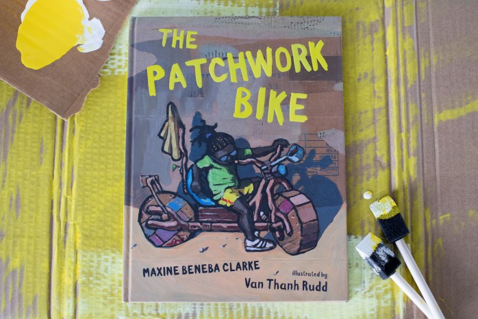 This is a promotional image of the book The Patchwork Bike. The book lays flat on painted cardboard with paintbrushes and wet paint next to it.