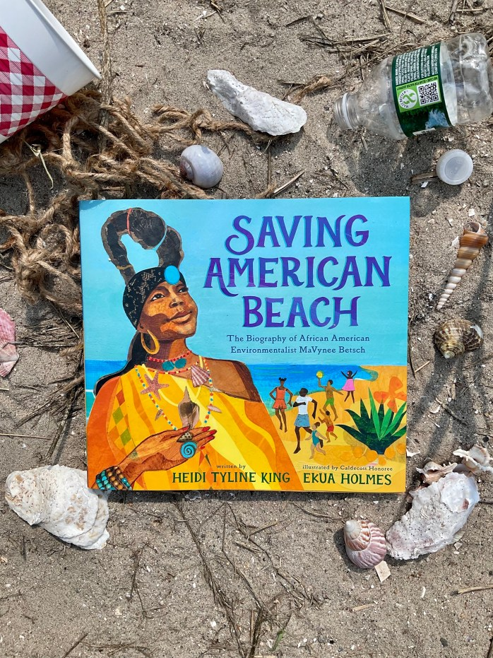 Promotional image of the book Saving American Beach: The Biography of African American Environmentalist MaVynee Betsch. The book is centered in the image, with shells and garbage around it. The book is resting in sand.
