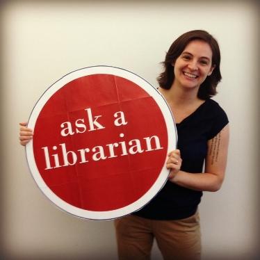 "desirae holding an ""ask a librarian"" sign"