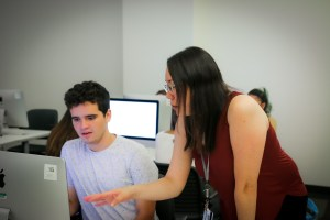 Librarian teaching LMU student in computer classroom