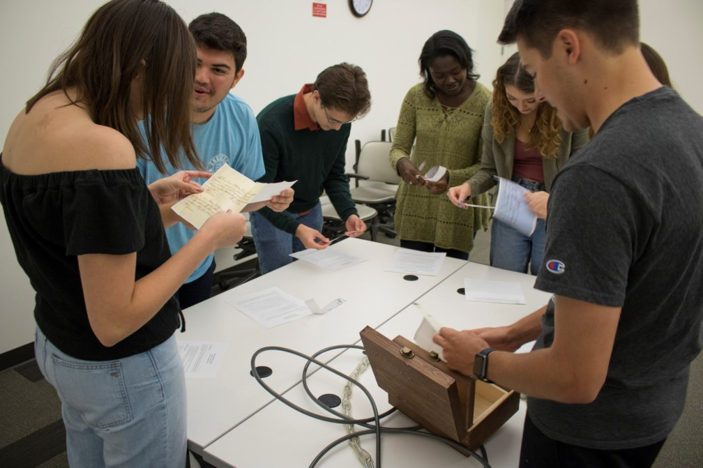 Students in our archives escape room trying to solve a puzzle