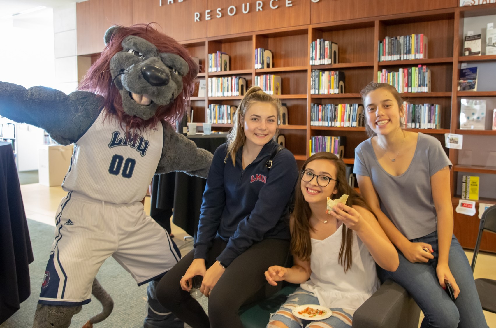 Iggy the Lion with three students in library