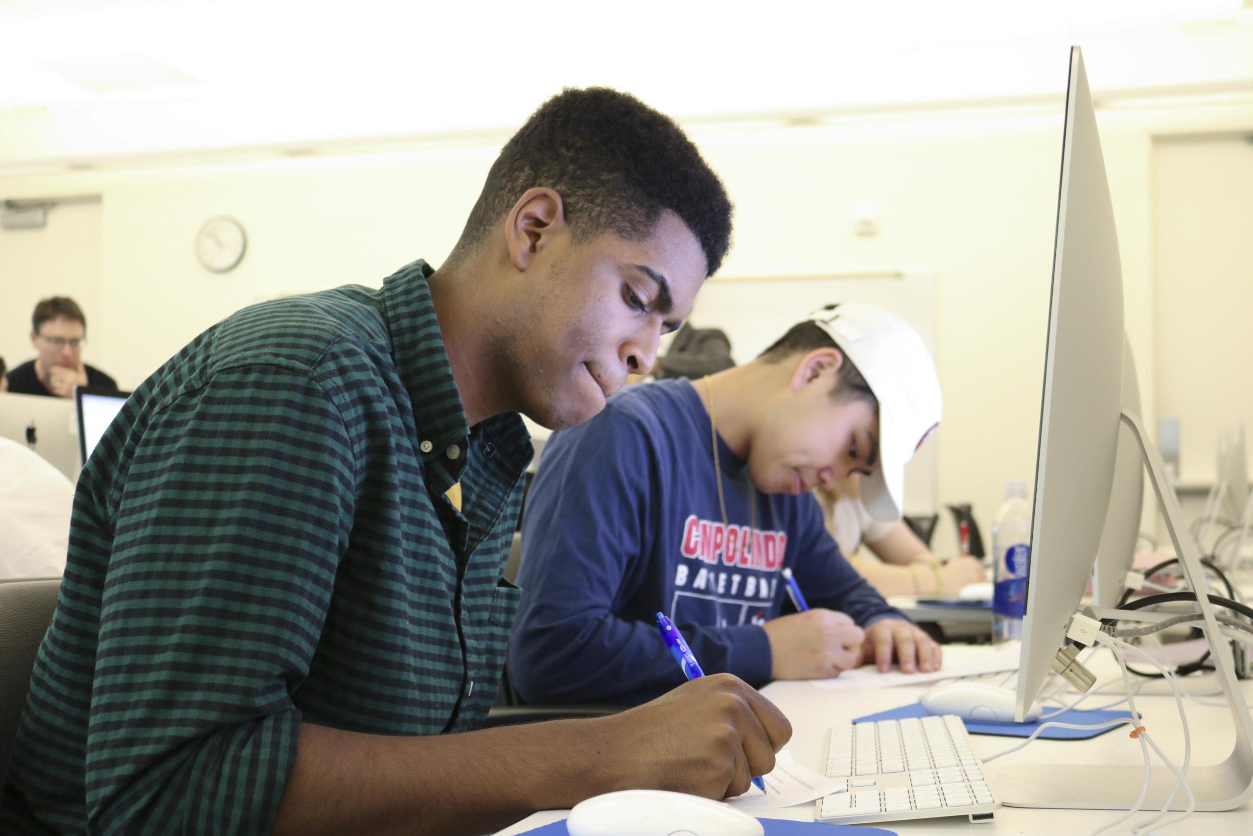 student writing at computer