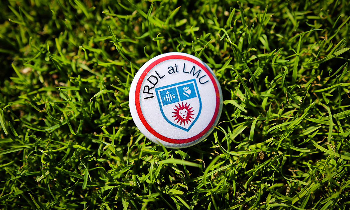 """""""IRDL at LMU"""" button laying on grass"""