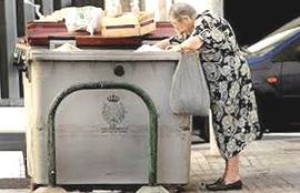 Una pensionata rovista nella spazzatura
