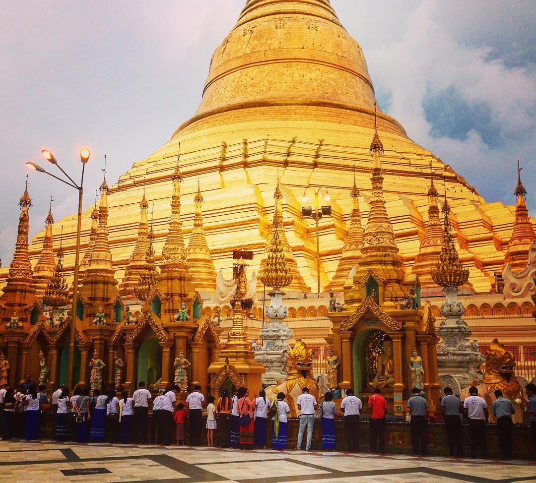 Rangoun, Birmanie. Pagode Shwedagon. Des fidèles allument des lampes au pied du stûpa.