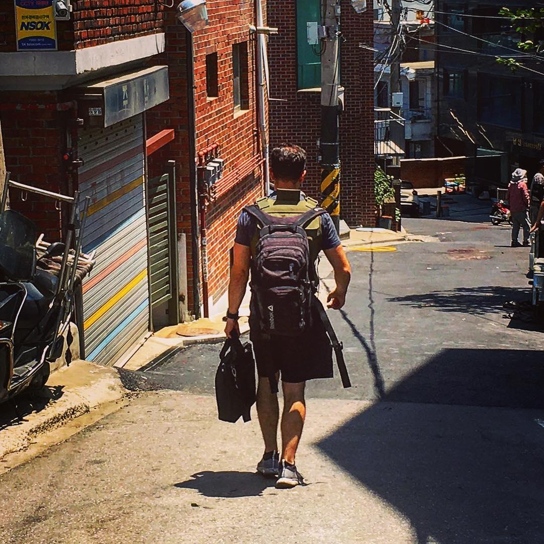 Séoul, Corée du Sud. Au détour d'une rue, je tombe sur ce drôle de type. Un occidental vêtu d'un short et d'un t-shirt noirs, il porte de surcroît un gilet pare-balles militaire orné de l'Union Jack et d'un nom, «James».