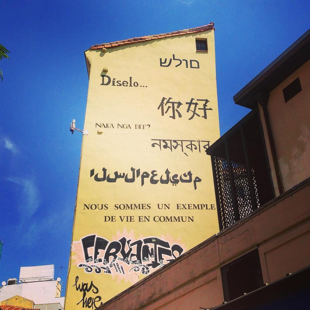 """Madrid, Royaume d'Espagne. Dans le quartier de Lavapiés, un message honorant la diversité et le vivre ensemble. Le problème, c'est que l'hébreu et l'arabe sont écrit à l'envers. """"Moulash"""" au lieu de """"Shalom"""", ça sonne plutôt comme un plat magyaro-mexicain, un mélange de goulash et de mole."""