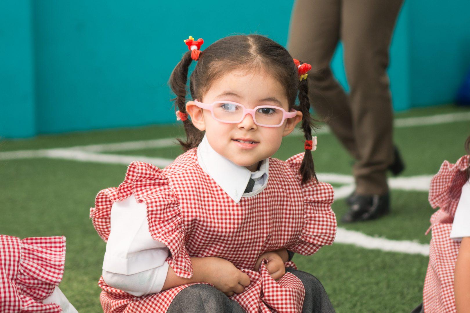niña con gafas y uniforme feliz