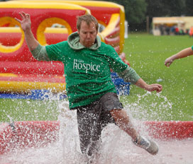 Jamie Gratton taking part in a wet & wild challenge at last summer's It's A Knockout competition for St Giles Hospice