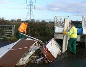 Workers clean up the dumped rubbish