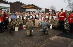 The knitted beanie hats are handed over outside The Staffordshire Regiment Museum