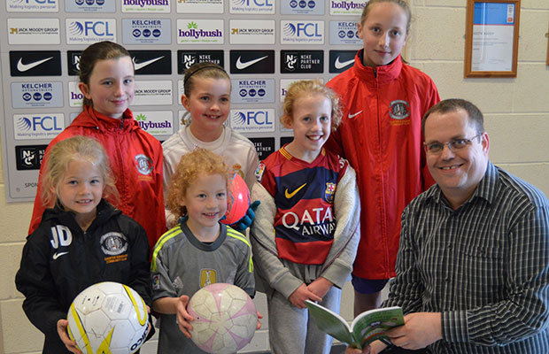 Paul Mullins handing over signed copies of his book to young footballers