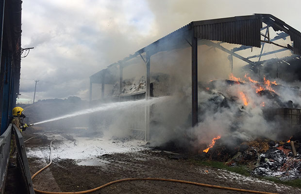 A firefighter dousing the flames in a barn at Yoxall