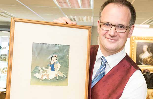 Charles Hanson with one of the cels from Snow White and the Seven Dwarfs