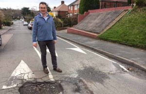 Cllr Paul Ray with one of the potholes on Dimbles Hill