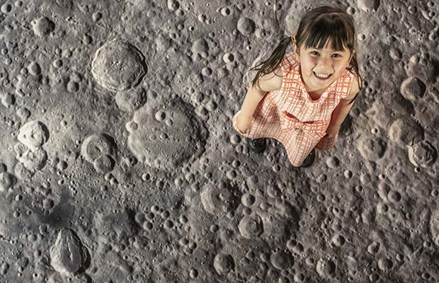 A girl on a projection of the moon surface in Lichfield Cathedral