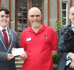 Ben Owen hands over the cheque to Border Collie Trust's Ben Wilkes with headteacher Dr Daryl Brown and school dog Lucy