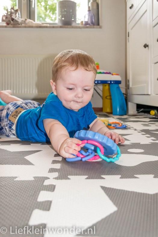 Jayden 6 maanden en 4 weken oud buik speelgoed pakken