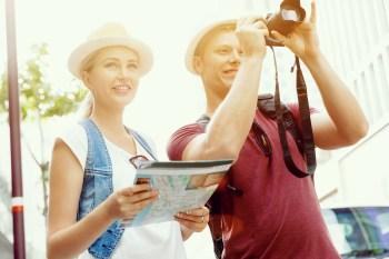 カメラを持つ男性と地図を持つ女性