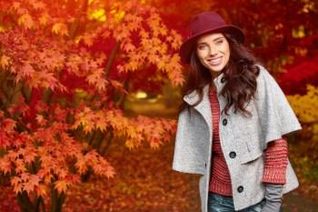 紅葉の中に立つ帽子の女性