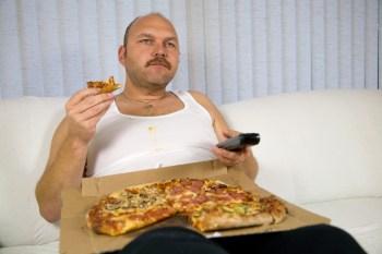 ピザを食べながらテレビを見るおじさん