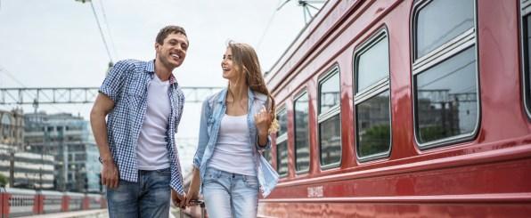汽車の前でスーツケースを持つカップル