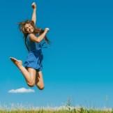 青空の下で飛び跳ねる女性