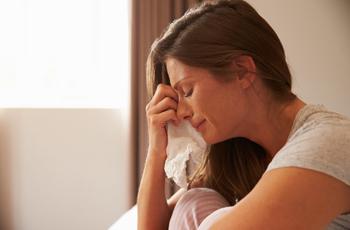 涙をハンカチで拭う女性