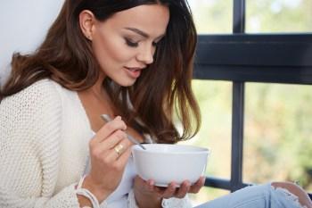 部屋でスープを飲む女性