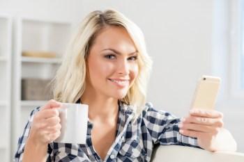 コーヒーカップを持ちながらスマホを見る女性