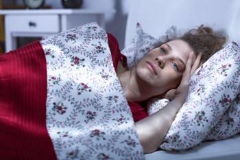 ベッドに横たわる暗い表情の女性
